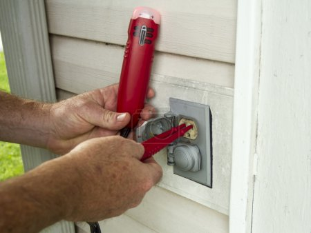 Electrician Testing A Outside Electrical Outlet