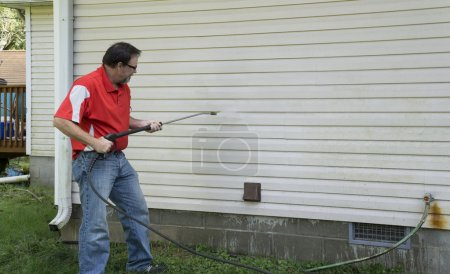 Contractor using a high pressure washer to remover...