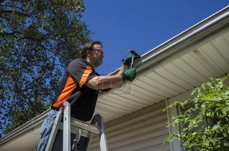 Worker Repairing A Gutter On A Customers Home