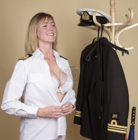 Photo for Female naval Lt Commander getting ready for duty. Buttoning her shirt - Royalty Free Image