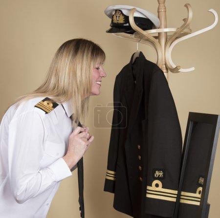 Photo pour Capitaine de vaisseau féminin se prépare pour le service Attachant sa cravate d'uniforme noire - image libre de droit