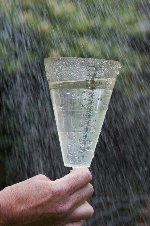 Photo pour Pluviométrie britannique excessive dans le pluviomètre UK Garden montrant 1,5 pouces d'eau - image libre de droit
