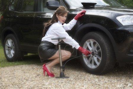 Female chauffeur checking tire of a black car