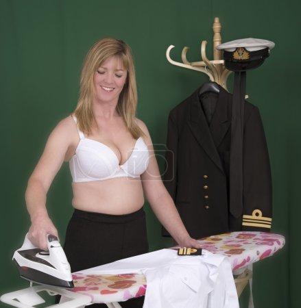 Photo pour Femme officier de marine repassage de son uniforme chemise blanche - image libre de droit