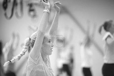 Photo pour Profil rapproché de la jeune femme bras levés, concept de fitness de groupe - image libre de droit