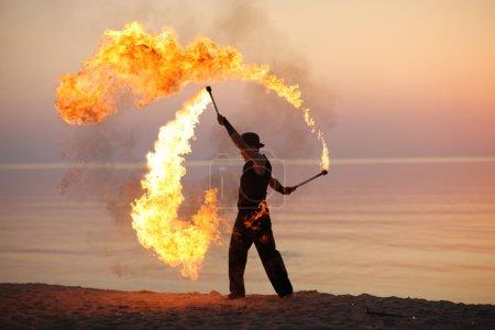 Photo pour Jongleur de feu professionnel performant sur la plage - image libre de droit