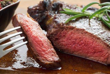 Photo pour Moyen steak côtelé rôti sur assiette en bois avec poivre et sel - image libre de droit