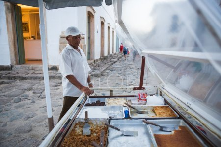 Man stands behind his food stall