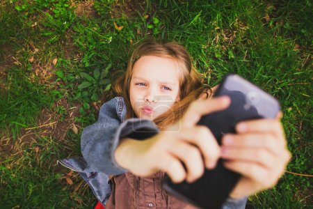 Photo for Young teenager girl taking selfie using mobile phone - Royalty Free Image