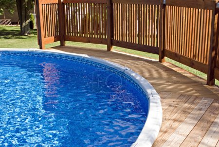 Photo for Round above-ground home pool with wooden deck and railing. - Royalty Free Image