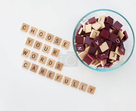 """Photo pour Col de verre avec bronzage en bois et lettres brunes. Mots épeler """"choisir vos mots avec soin """". - image libre de droit"""