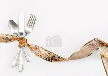 Photo for Silverware tied with festive holiday bronze and gold ribbon isolated on white background. - Royalty Free Image