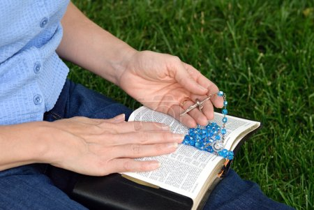 Hands with Rosary on Bible