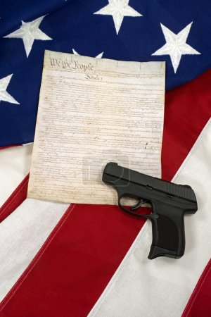 Constitution with Hand Gun on American Flag, Vertical