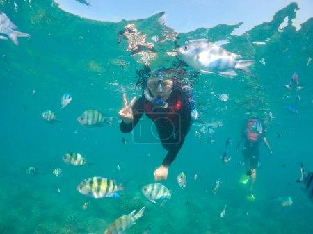 Photo pour Femme plongée avec tuba avec des poissons. Moment sous-marin - image libre de droit