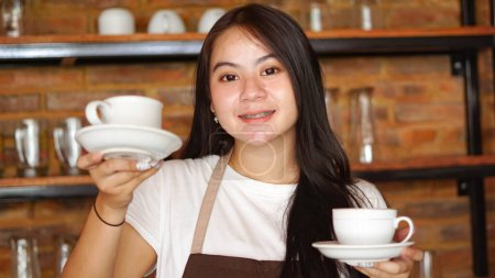 Photo for Asian woman barista holding cup for coffee - Royalty Free Image
