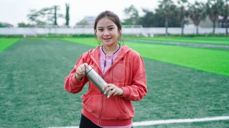 Photo for Asian runner woman drinking water at stadion - Royalty Free Image