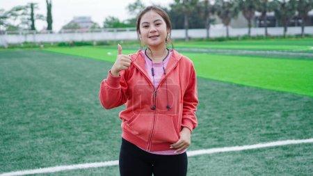 Photo pour Asiatique coureur femme portant veste et écouteur OK geste - image libre de droit