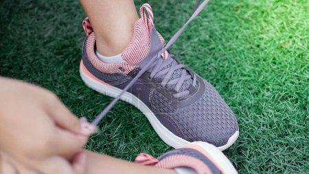 Photo for Asian woman tying sneakers before running. Close up legs - Royalty Free Image
