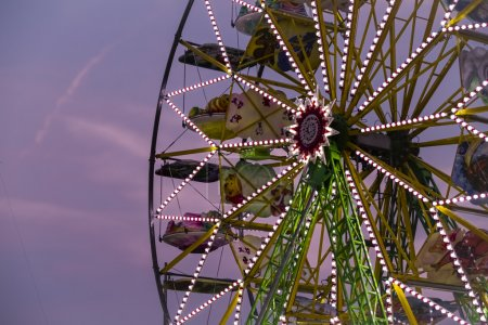 Big ferris Wheel at night during sunset in summer time