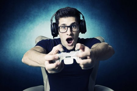 Photo for Videogame addicted young guy playing with console - Royalty Free Image