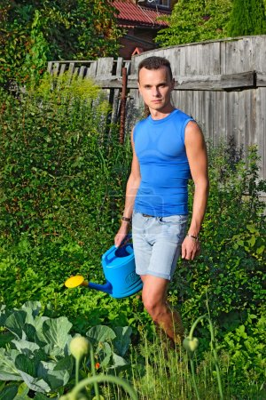 A young man with a blue watering can around the garden with cabbage on the farm in summer Sunny day