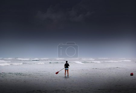 Silhouettes of Stand up paddle surfer at overcast sea