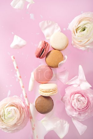 Photo for Multi-colored macarons with milk and flowers - Royalty Free Image