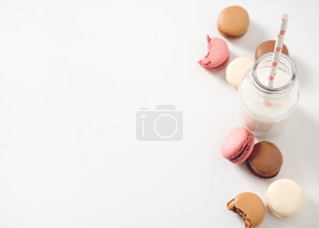 Photo for Multi-colored macarons with milk in a bottle - Royalty Free Image