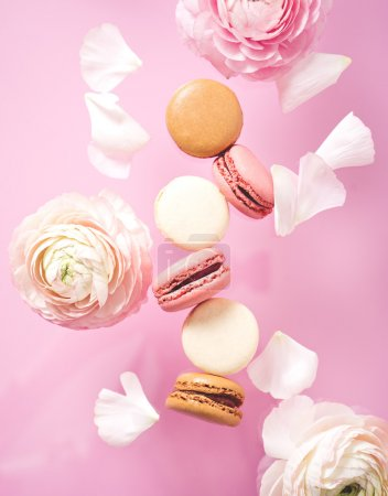 Photo for Some  macaroons with flowers  lying on pink background - Royalty Free Image