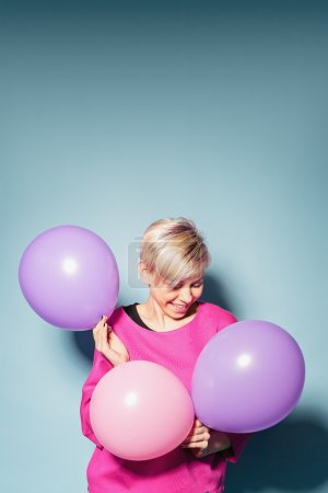 Girl have fun with colored balloons on blue background