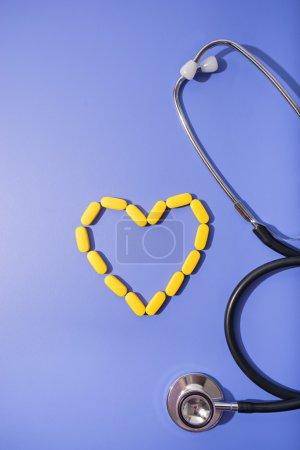 Photo pour Image de pilules et stéthoscope sur table bleue - image libre de droit