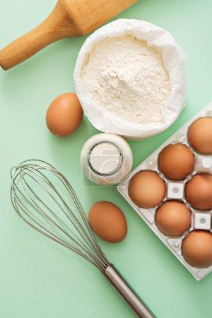 Photo pour Lait, œufs, farine et outils de cuisine sur table verte - image libre de droit