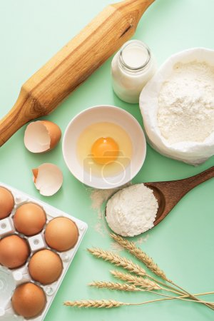Photo for Milk, eggs, flour and kitchen tools on green table - Royalty Free Image