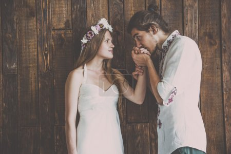 Young and beautiful bride and groom are having a good fun time and happy together while shooting a wedding photosession in studio with rustic decorations and wooden backgrounds