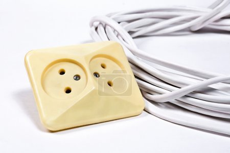 Wall sockets and power cable on white surface