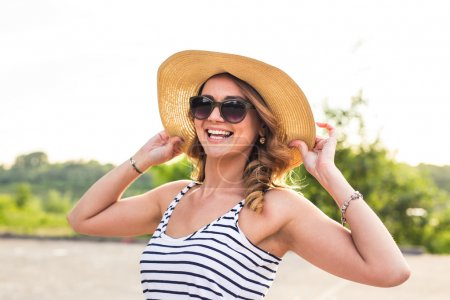 Portrait of elegant lady in hat on summer vacation