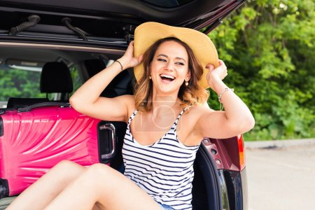 Cheerful woman on summer travel vacation sitting in a car trunk.