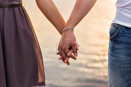 Photo for Happy couple holding hands in the sunset - Royalty Free Image