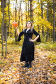 portrait of beautiful blond young woman holding pumpkin in forest. Halloween day