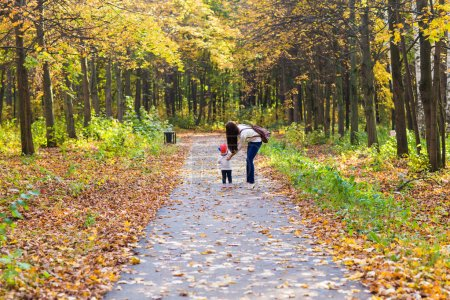 Young mother walking with her baby in an autumn park