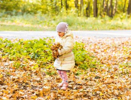 Photo pour Petite fille à feuille jaune. Enfant jouant avec des feuilles dorées d'automne. Les enfants jouent dehors dans le parc. Randonnées pédestres en forêt automnale. Enfant en bas âge sous un érable par une journée ensoleillée d'octobre - image libre de droit