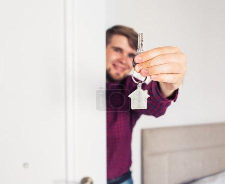 Holding out house keys. Housewarming