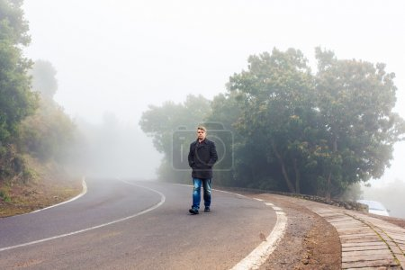Photo for Alone man walking in a misty forest - Royalty Free Image