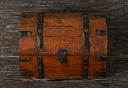 Photo for Old closed wooden chest on dark wooden table, top view - Royalty Free Image