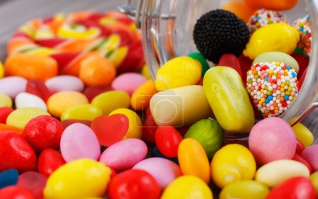Photo for Closeup colorful candies in jar. Candies scattered on the wooden table - Royalty Free Image