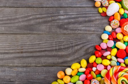 Colorful candies scattered on the wooden table
