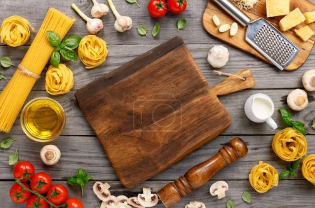 Photo for Spaghetti and fettuccine with different ingredients for cooking pasta on wooden table with blank of wooden kitchen board, top view. Rustic style. Flat lay - Royalty Free Image