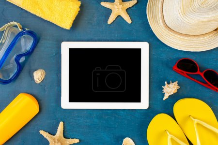 Photo for Tablet with blank screen on blue surface with beach items, top view - Royalty Free Image