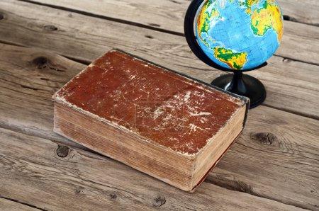 Photo pour Livre vintage fermé avec un globe sur une table en bois close up. Vue de dessus. Espace de copie. Espace libre pour tex - image libre de droit